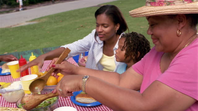 Medium shot mother, daughter and grandmother arranging food on picnic table