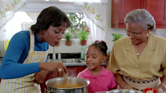 Medium shot mother, daughter and grandmother cooking in kitchen / mother tasting sauce