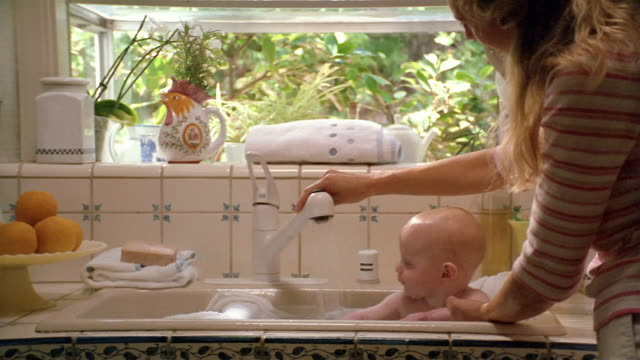 Medium shot mother giving baby bath in kitchen sink / baby playing with running water from faucet