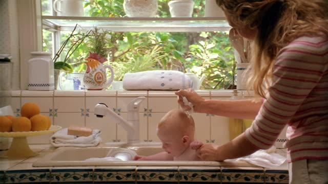 Medium shot mother giving baby bath in kitchen sink