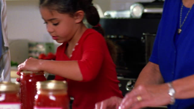 medium shot mother, grandmother and daughter sealing tomato sauce into canning jars in kitchen - domestic kitchen stock-videos und b-roll-filmmaterial