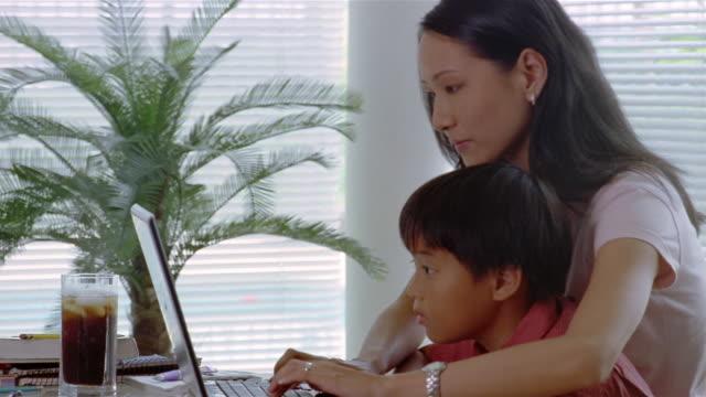 Medium shot mother helping son use laptop computer