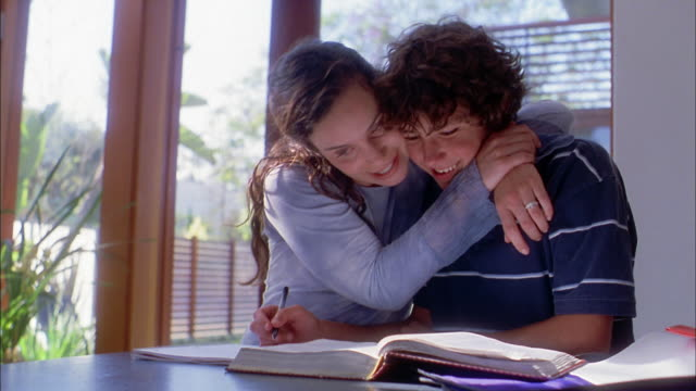 Medium shot mother helping son w/homework and hugging him