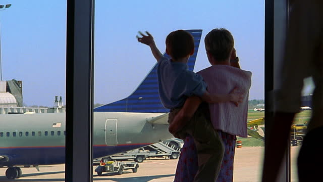 medium shot mother holding boy / mother and son waving at airplane out window - 手を振る点の映像素材/bロール