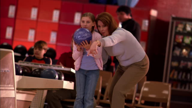 Medium shot mother pointing and instructing daughter w/bowling ball