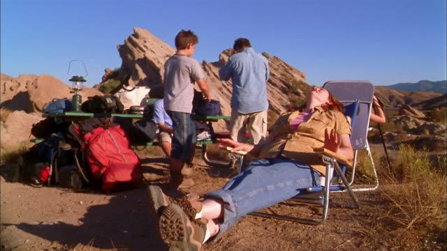 vídeos y material grabado en eventos de stock de medium shot mother sitting in canvas lounge chair / family unpacking supplies - tumbona