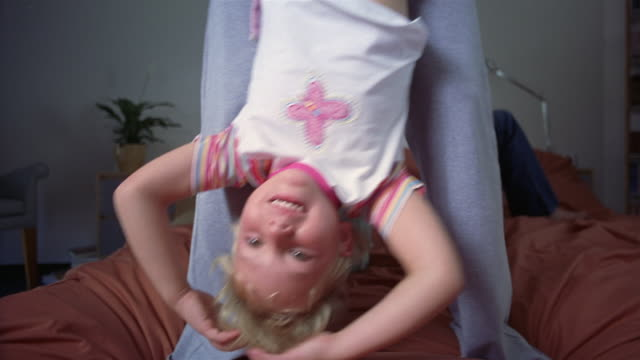 medium shot mother swinging daughter upside down on bed / father lying and son jumping on bed / south africa - upside down stock videos & royalty-free footage
