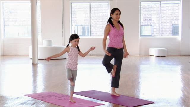 vídeos y material grabado en eventos de stock de medium shot mother teaching yoga to daughter/ brooklyn, new york - vriksha asana