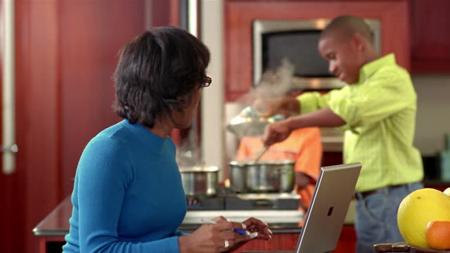 medium shot mother working on laptop in kitchen / two sons cooking in background - pen stock videos & royalty-free footage
