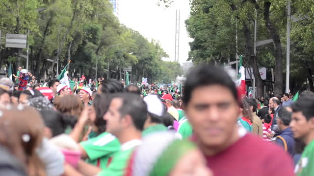 medium shot, moving handheld camera. the crowd is celebrating running and jumping. the riot police guards the angel de la independencia . the street... - staring stock videos & royalty-free footage