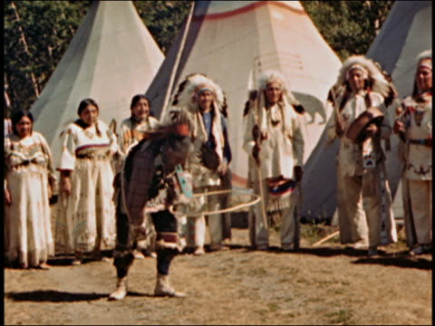 medium shot native american man performing hoop dance while group of people watch w/tents in background / audio - indigenous north american culture stock videos & royalty-free footage