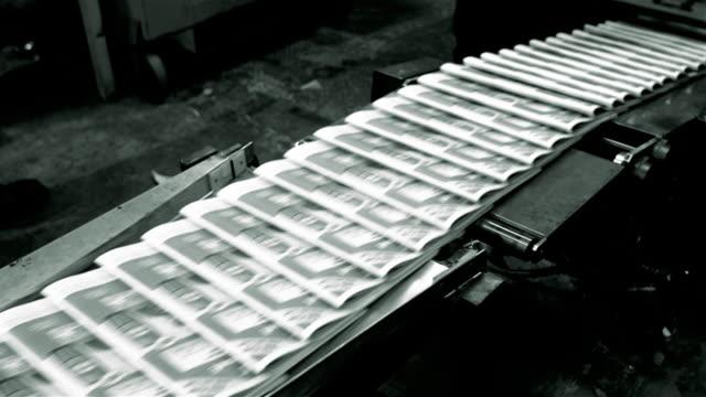 Medium shot newly printed copies of Santa Barbara News Press moving on conveyer belt / Santa Barbara, California