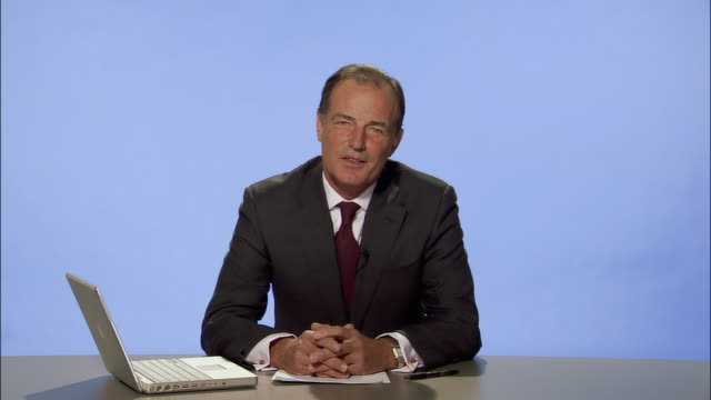 medium shot news presenter holding papers and looking at laptop/ turning head and talking to camera with hands clasped/ looking away/ london - hands clasped stock videos and b-roll footage