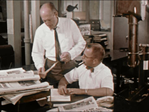 1964 medium shot newspaper editor at New York Newsday smokes pipe and confers with fellow worker / Long Island, New York / AUDIO