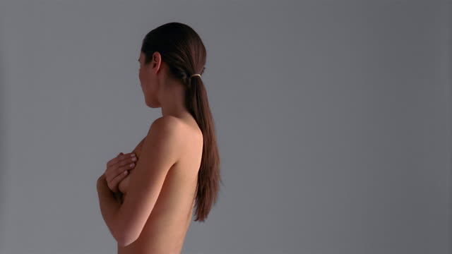 stockvideo's en b-roll-footage met medium shot nude woman covering chest standing on spinning turntablemedium shot nude woman covering chest standing on spinning turntable / london - borstkas