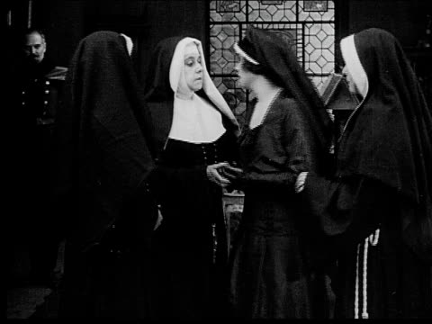 vídeos de stock, filmes e b-roll de 1916 b/w medium shot nuns kissing and saying goodbye to young woman in church - nun