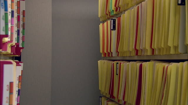 Medium shot nurse looking for file in filing room in doctor's office / selecting file and walking away