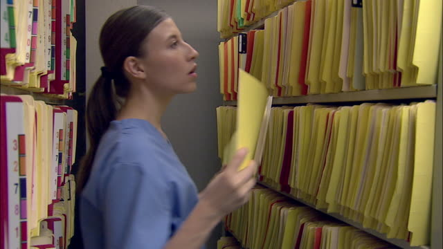 stockvideo's en b-roll-footage met medium shot nurse replacing files in filing room in doctor's office - operatiekleding