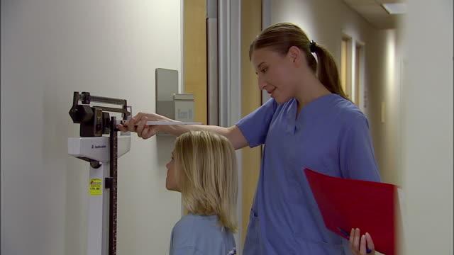 vidéos et rushes de medium shot nurse weighing young boy and measuring his height - mesurer