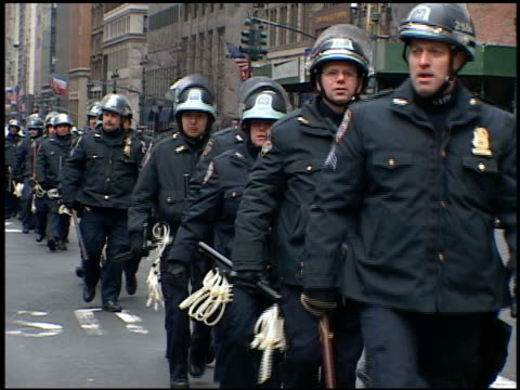 2003 medium shot nypd policemen march in single file on 5th ave in front of ny public library / new york city - friedensdemonstration stock-videos und b-roll-filmmaterial