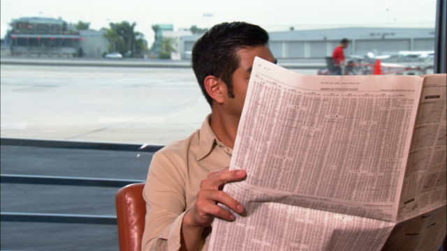 vídeos y material grabado en eventos de stock de medium shot obscured man reading newspaper near window at airport - cara oculta