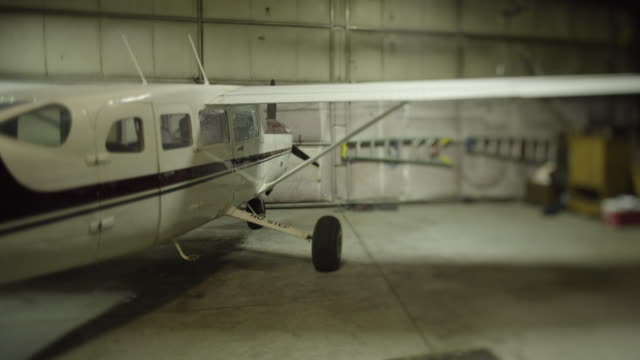 medium shot of a airplane in a hangar - 飛行機格納庫点の映像素材/bロール