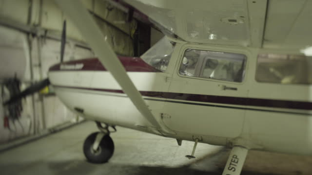 medium shot of a airplane in a hangar - landefahrwerk stock-videos und b-roll-filmmaterial