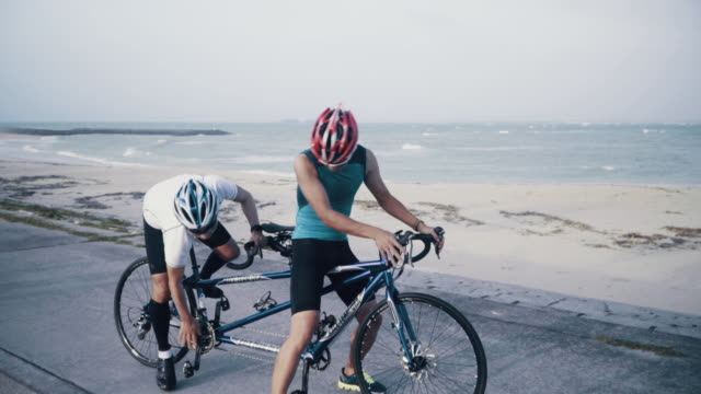 Medium shot of a blind triathlete and his guide training on their tandem bicycle
