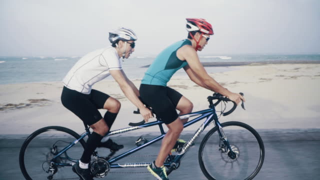 medium shot of a blind triathlete and his guide training on their tandem bicycle - visual impairment stock videos & royalty-free footage