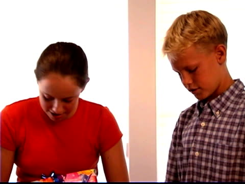 medium shot of a boy and girl standing and wrapping presents. - bald head island stock videos & royalty-free footage
