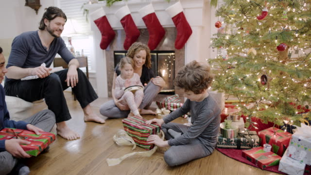 medium shot of a boy unwrapping his present at christmas - unwrapping stock-videos und b-roll-filmmaterial