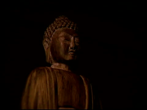 medium shot of a buddhist statue made of carved wood. - female likeness stock videos & royalty-free footage