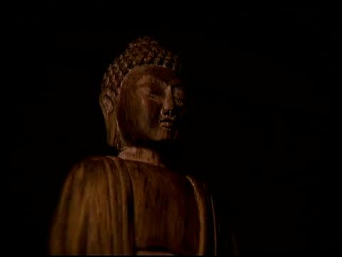 medium shot of a buddhist statue made of carved wood. - weibliche figur stock-videos und b-roll-filmmaterial