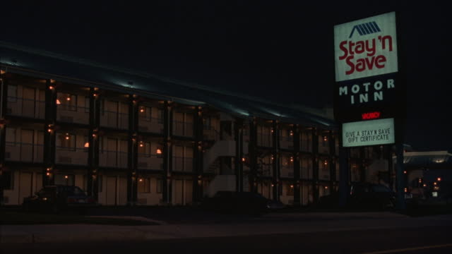 medium shot of a car turning into a motel parking lot at night. - motel stock videos and b-roll footage