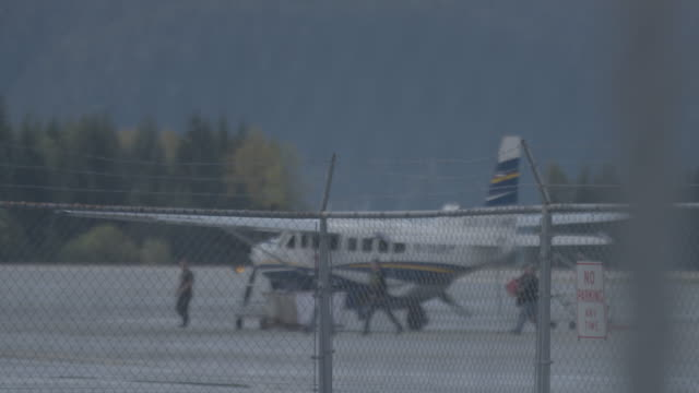 medium shot of a chain link fence with an airplane in the background at juneau international airport - juneau stock videos and b-roll footage