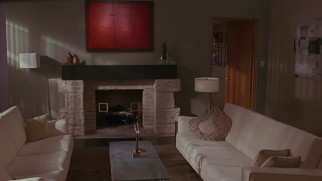 Medium shot of a contemporary living room with two white couches facing each other and a white brick fireplace.