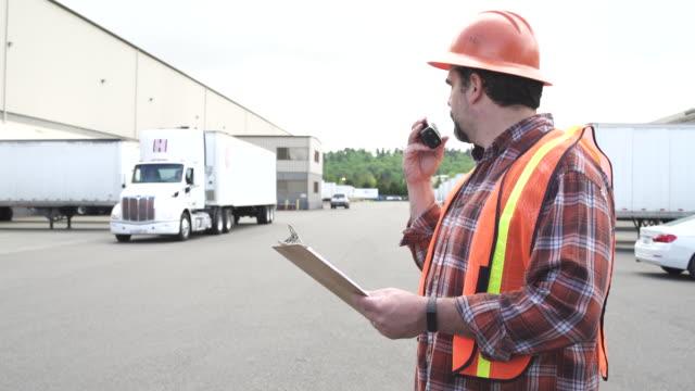 vídeos y material grabado en eventos de stock de medium shot of a control worker in a truck parking lot - toma mediana