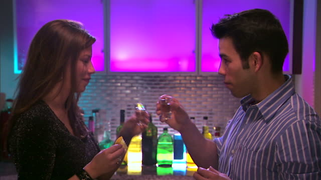 Medium shot of a couple doing tequila shots in a bar.