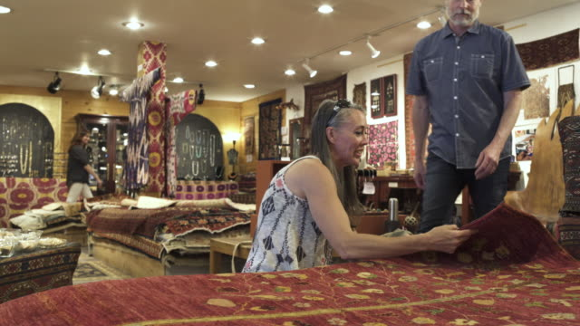medium shot of a couple looking at carpets in a shop - ラグ点の映像素材/bロール