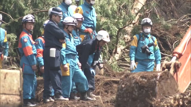 Medium shot of a crane car and rescuers clearing debris in and around collapsed house after huge landslide buried houses in Minami Aso Village during...
