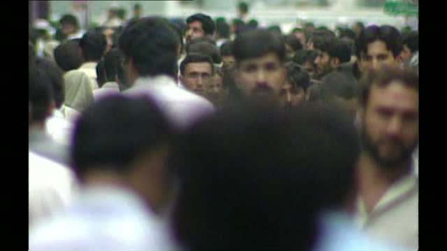 medium shot of a crowd of men walking along a street in islamabad; 14th september, 2001. - black hair stock videos & royalty-free footage