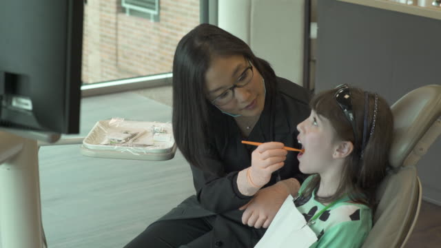 vídeos y material grabado en eventos de stock de medium shot of a dentist examining a girl - disposable gloves
