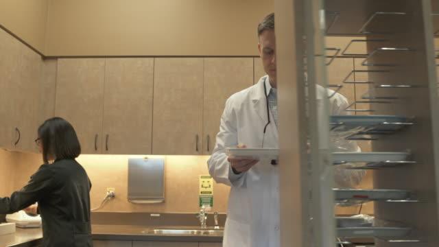 vídeos de stock e filmes b-roll de medium shot of a dentist walking away with a tray - só um homem de idade mediana