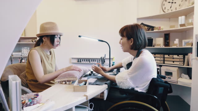 medium shot of a disabled woman working on a customers nails in a her own beauty salon - 身体障害点の映像素材/bロール