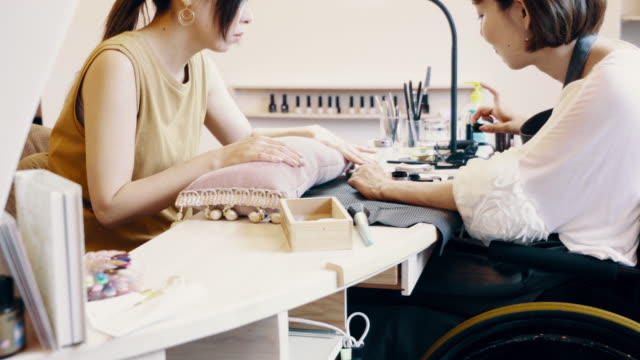 vidéos et rushes de medium shot of a disabled woman working on a customers nails in a her own beauty salon - manucure