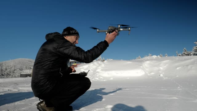 Medium Shot of a Drone Pilot while Flying with his Drone in Wintertime, Take-off, Landing and Using the Remote Control, Solo Traveler, Adventurous Hobby, 4k resolution