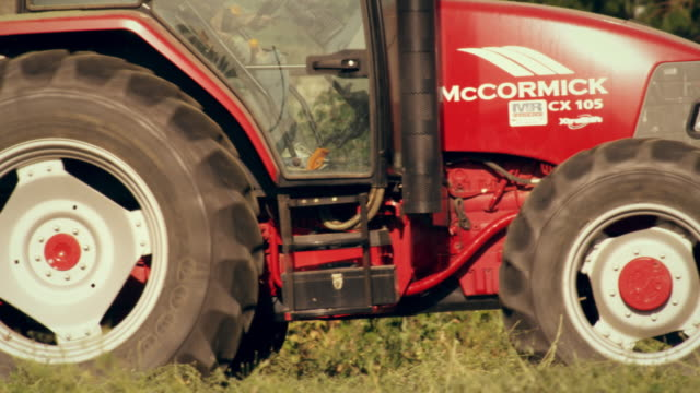 medium shot of a farmer driving a hay baler as he goes around the farm - hay baler stock videos & royalty-free footage