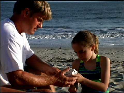 medium shot of a father and daughter sitting on a beach together looking at a sea shell. - see other clips from this shoot 1135 stock videos & royalty-free footage