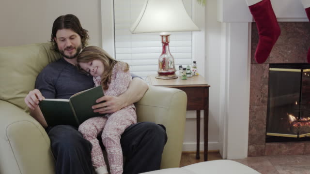 Medium shot of a father storytelling for his daughter
