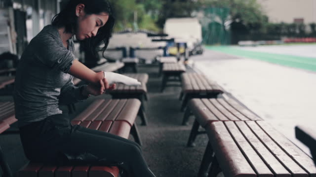 medium shot of a female adaptive athlete fitting her prosthetic arm before training for competition - 大学点の映像素材/bロール